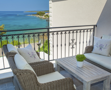 Cozy balcony of the upper apartment with balcony furniture and lovely Mediterranean details